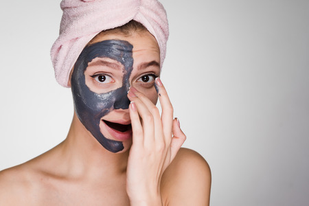 a young beautiful girl with a pink towel on her head applied a clay mask to half the face
