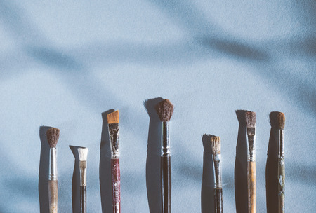 on a blue background there are artistic brushes of different sizes