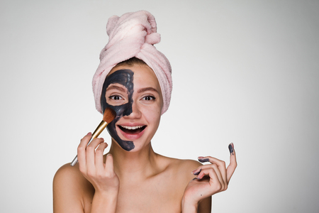 Laughing beautiful girl with a pink towel on her head puts on half face clay mask