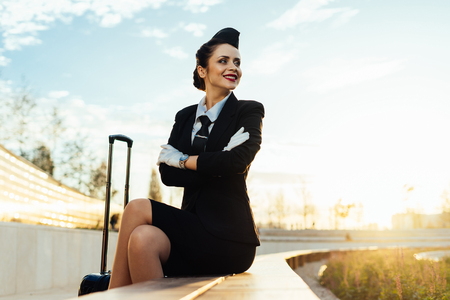happy young stewardess girl in uniform sits in park, with suitcase, waiting for airplane 版權商用圖片