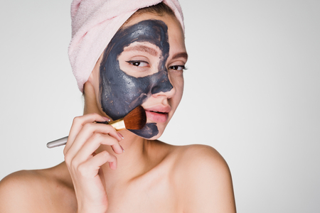 a young attractive girl with a pink towel on her head applied a clay mask to half the face