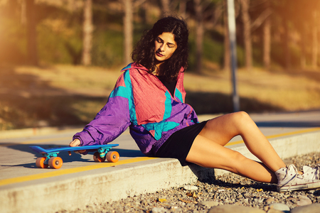 young stylish girl sits on the asphalt, near the longboard Stock Photo