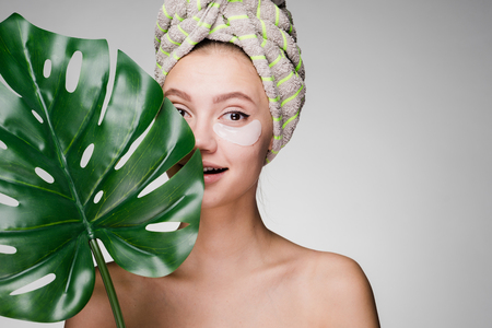 beautiful smiling girl with a towel on her head holding a green leaf, day spa.under her eyes white patches