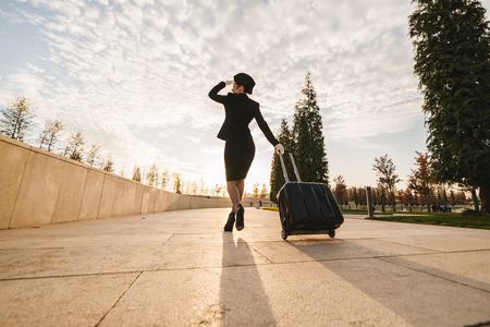 slender young woman stewardess in uniform goes on a flight with a suitcase