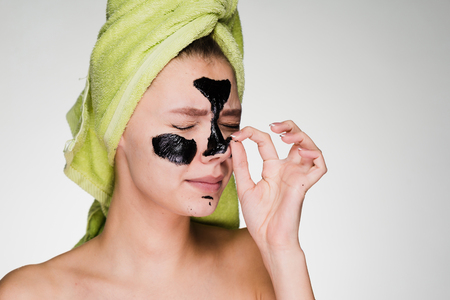a young disgruntled girl with a green towel on her head removes a black cleansing mask from her face, she is uncomfortable