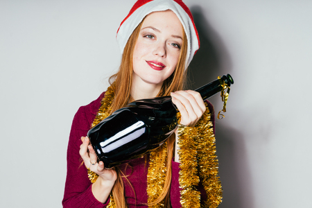 beautiful red-haired girl in a red cap like Santa Claus celebrates the new year, holding a bottle of champagne