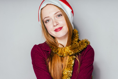 lovely red-haired girl with a red cap like Santa Claus waiting for a new year and Christmas