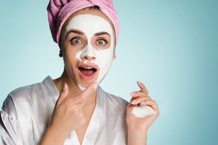 surprised happy girl with a towel on her head puts on face a white nutritious mask
