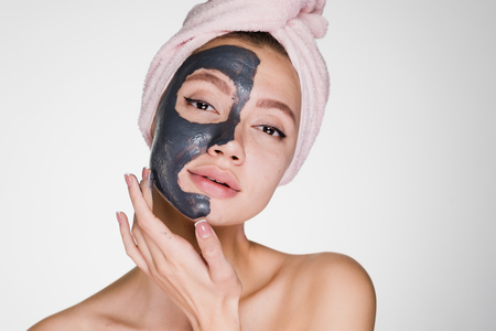 An attractive young girl with a pink towel on her head applied a useful clay mask