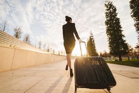 fiduciosa snella hostess donna in uniforme va su un volo con una valigia sotto i raggi del sole