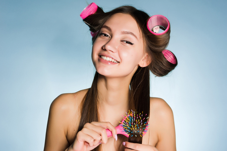 young girl on a white background combing her hair smiling Stock Photo