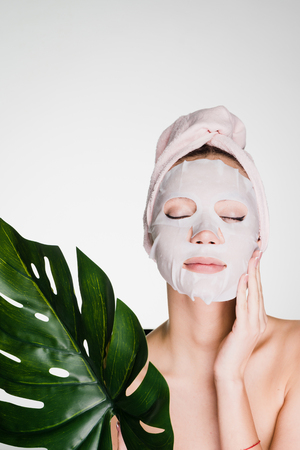 young girl with a towel on her head, on her face a tissue mask, a spa procedure Foto de archivo