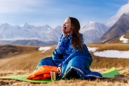 young girl yawns in the background of the Caucasian mountains, travels Stock Photo