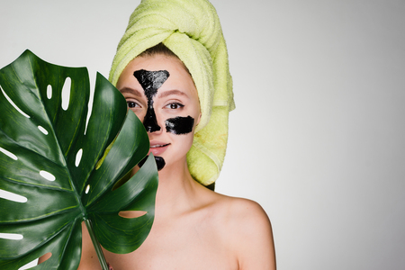 A cute young girl with a green towel on her head applied a black cleansing mask to the problem areas on her face Stock Photo