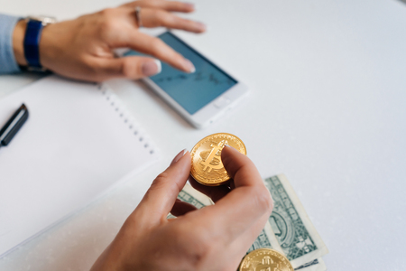 the girl financier studies the graphics of the crypto currency, keeps the gold bitcoin