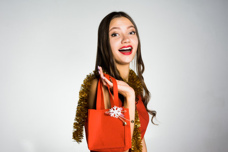happy smiling girl with red lipstick received an expensive fashionable bag for the new year