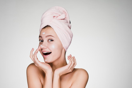 happy girl with a towel on her head on a gray background