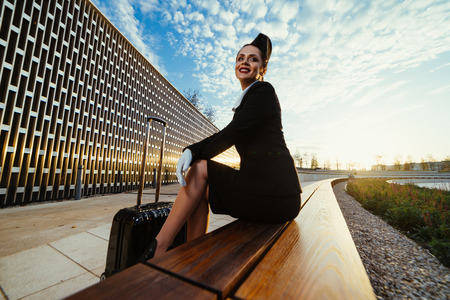 slender young woman stewardess sitting on bench in park, with suitcase, waiting for her flight