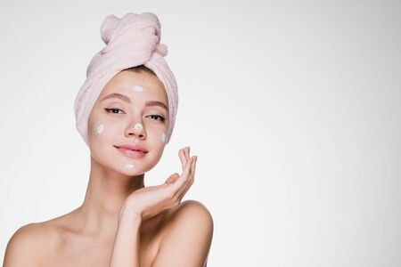 cute attractive girl with pink towel on her head applying white moisturizer on face
