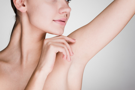 young girl on a white background caring for the skin underarms Stockfoto