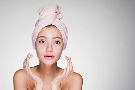 cute young girl with pink towel on her head applying white nourishing cream on face Stock Photo