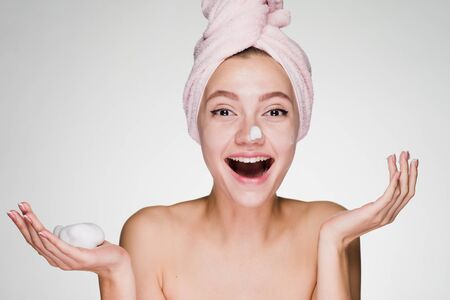 young smiling girl puts on face a white mask Stock Photo