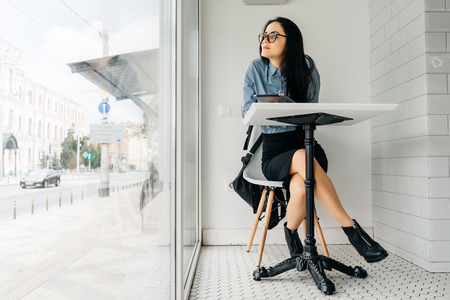 girl in glasses sits at a table on the background of a large window