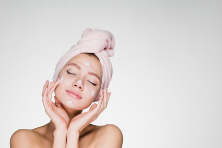 a cute young girl with a towel on her head puts a nourishing cream on her face, her eyes are closed, she enjoys 写真素材