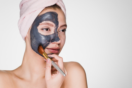 a young girl puts on her face a black mask