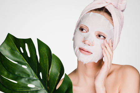 girl with a towel on her head put a mask on her face