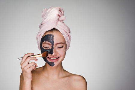 young girl with a towel on her head apply on face mask Stock Photo