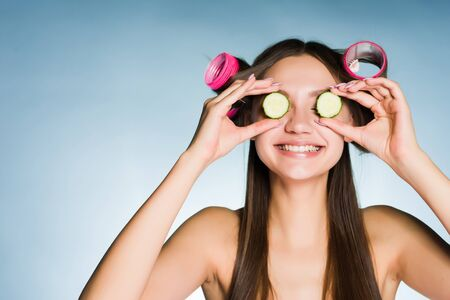 young girl in curlers smiling closes her eyes slices of cucumber