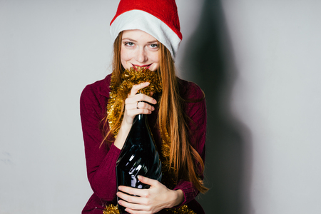 a young girl in a New Years suit holds a large bottle of champagne in her hands