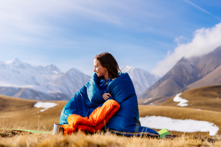 young girl in a sleeping bag on a background of mountains