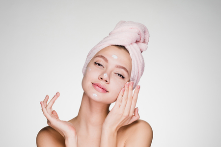 cute young girl with pink towel on her head applying white moisturizer on face