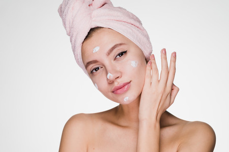 young attractive girl with pink towel on her head applies white moisturizer on face Stock Photo