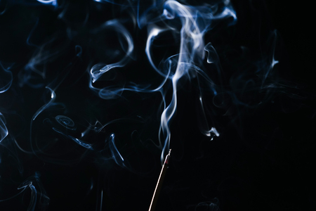 smoldering aromatic stick in the dark, a lot of blue smoke Stock Photo