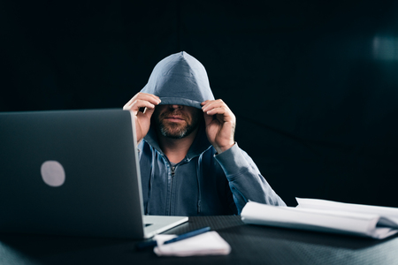 criminal bearded man hides his face under the hood, sits in the dark next to the laptop