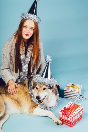 a cute red-haired girl with a cap on her head sits on the floor with her dog, celebrates a new year and Christmas