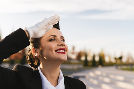 happy smiling woman stewardess in uniform looks up into the sky, waiting for airplane