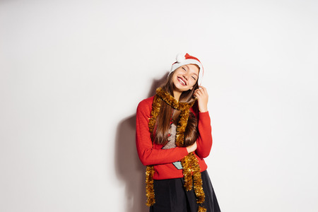 happy laughing girl in a red cap and with a gold tinsel around her neck celebrating the new year 2018 and Christmas