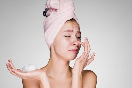Funny young girl with a pink towel on her head applies a cleansing foam on her face Stock Photo