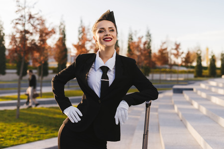 attractive happy stewardess girl in uniform with a suitcase waiting for her plane in the park, smiling, thinking about the sky