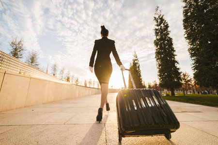 a slender young woman of a stewardess in uniform with a suitcase goes on a flight