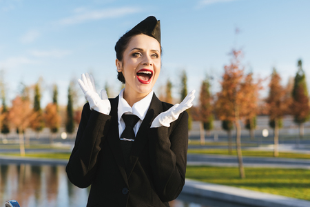 happy beautiful stewardess girl in uniform is happy with something then