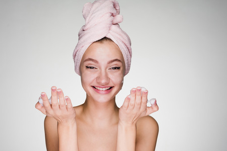 happy woman with a towel on her head put on face foam Stock Photo
