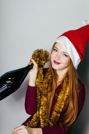 happy red-haired girl celebrates the new year 2018, on her head a red cap like Santa Claus, holds a bottle of champagne Stock Photo