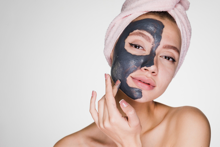 a nice young girl with a pink towel on her head has put a clay mask on half of her face Stock Photo