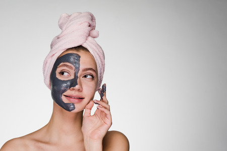 a nice girl with a pink towel on her head applied a clay mask to half of her face, looks away dreamily