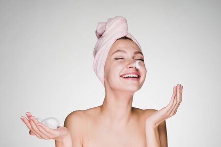 happy laughing girl with pink towel on head applying cleansing foam on face